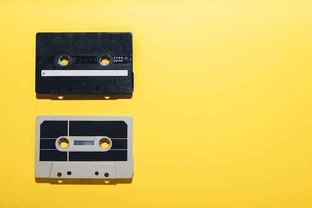 黄色の背景に分離された2本のオーディオカセットテープコピースペース
