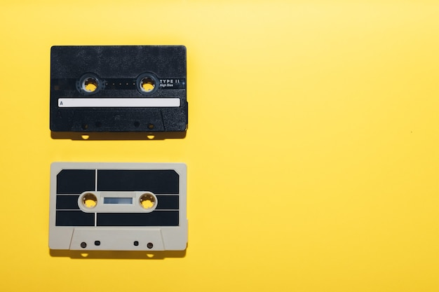 Two audio cassette tapes isolated on a yellow background copy space