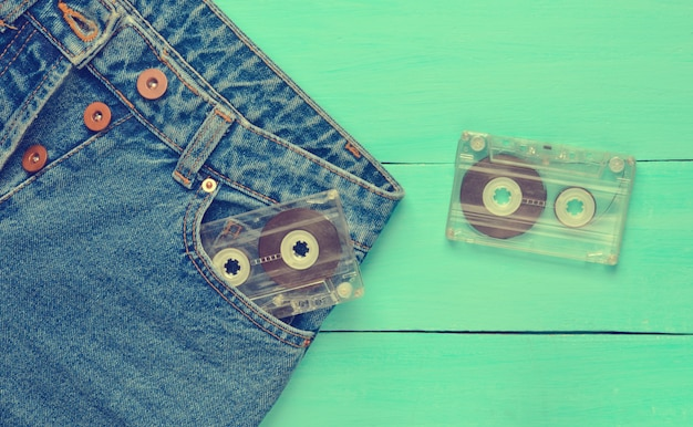 Two audio cassettes in a jeans pocket on a blue wooden surface