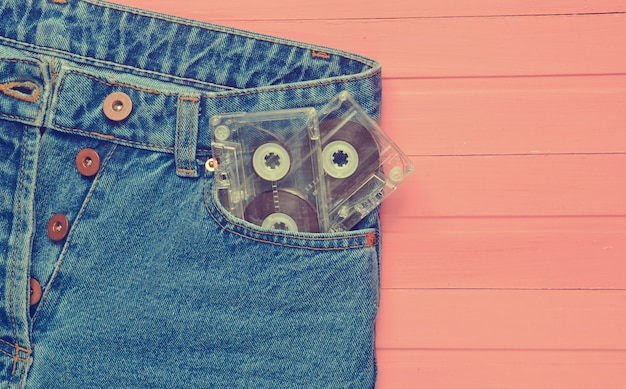 Two audio cassettes in a jeans pocket on a pink wooden surface