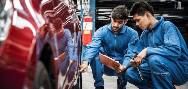 Two auto mechanic doing car service and maintenance.