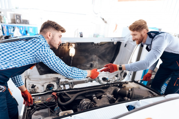 Two auto mechanics are looking under the hood.