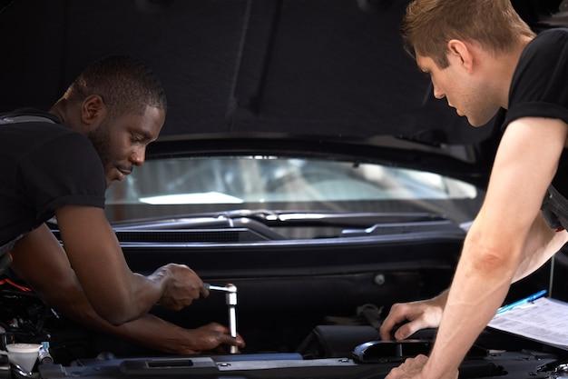 2人の自動車機械の同僚が何をすべきかについて話し合う