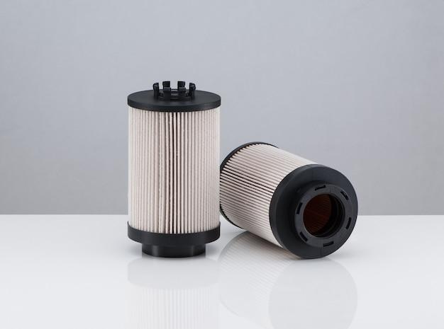 Два автомобильных фильтра цилиндрической формы на белом фоне с отражением
