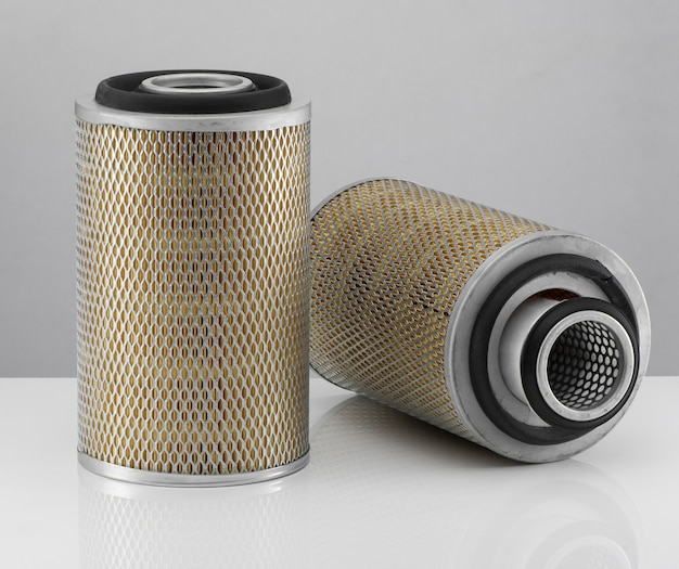 Two automotive filter cylindrical shape  on a white background with reflection