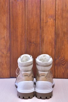 Two autumn or winter boots stand near a wooden brown background back