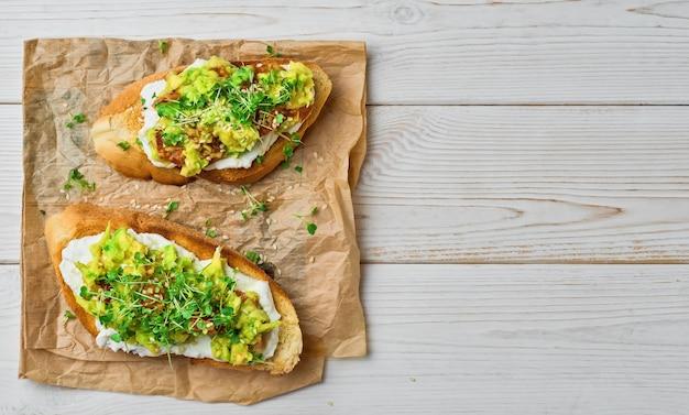 Два бутерброда с авокадо, помидоры, микрозелень и кунжут на тосте из багета со сливочным сыром на бумажной подкладке, белый деревянный стол. вид сверху с копией пространства. вегетарианские тосты