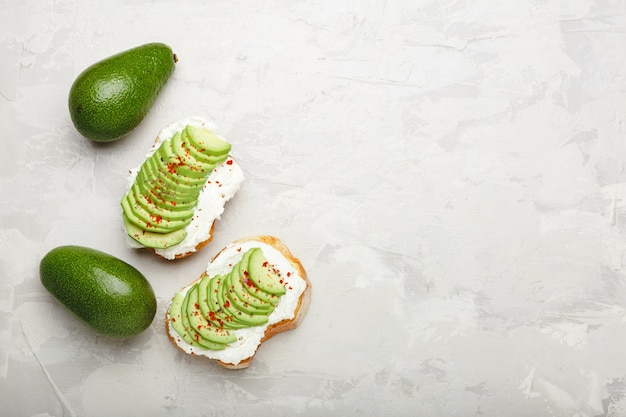 Two avocado toasts, avocado sandwich. fresh avocado sliced on toast of wheat bread, cream cheese. avocado sprinkled with chili, basil spices