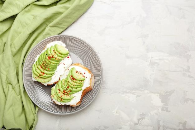 Two avocado toasts, avocado sandwich. fresh avocado sliced on toast of wheat bread, cream cheese.