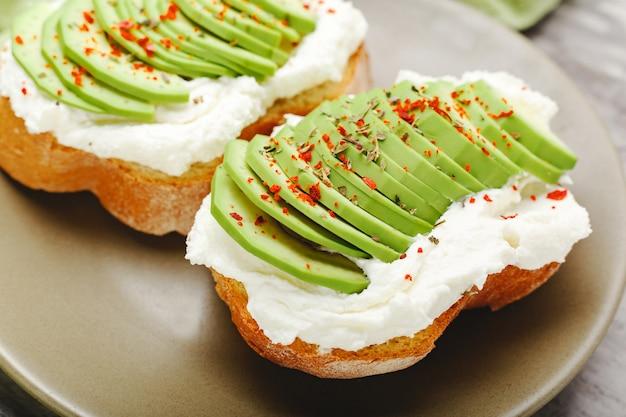 Two avocado toasts on green plate, avocado sandwich. fresh avocado sliced on toast of wheat bread, cream cheese.