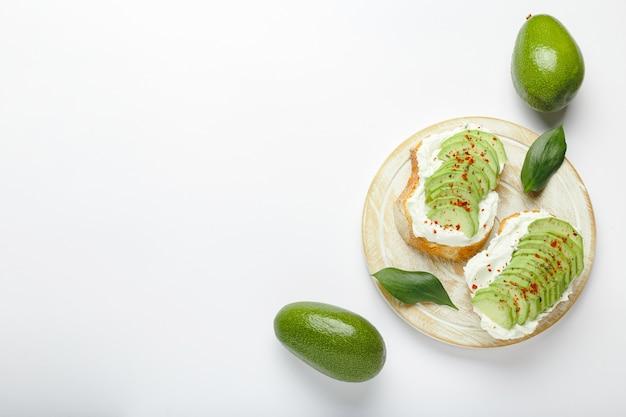 Two avocado toasts on white background