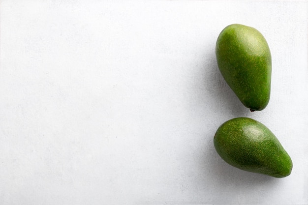 Two avocados on a white table, top view, copy space