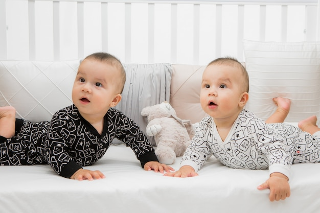 Two babies in bed on grey