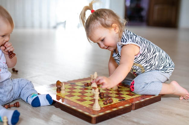 Мальчик и девушка 2 младенцев играя шахмат на белом деревянном поле дома.