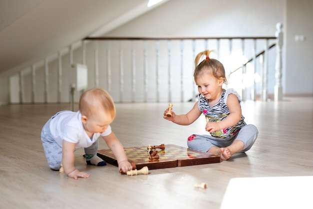 Two babies boy and girl playing chess on the white wooden floor at home.