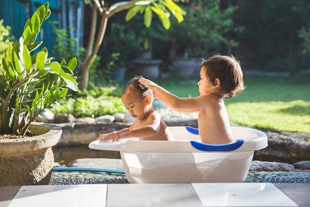 Двое детей вместе принимают ванну