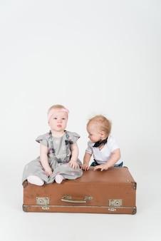 Два младенца с чемоданом на белом пространстве