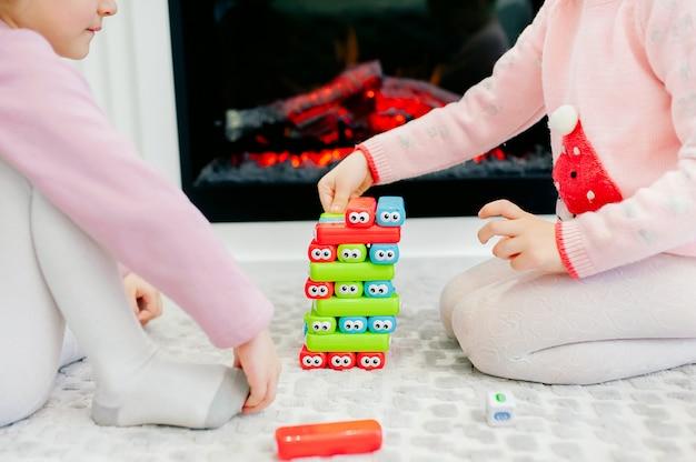 두 여자 아기는 어린이 게임 정을 재생합니다. 젠가 타워에서 한 조각을 꺼내십시오. 탑에서 젠가 조각을 조심스럽게 제거하십시오. 보드 게임