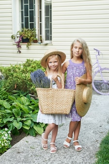 Two baby girls in hats with a basket of lavender in a summer garden