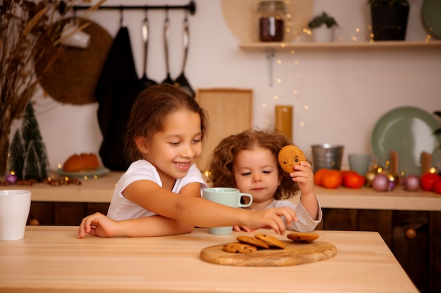 Two baby girls having breakfast in the christmas kitchen
