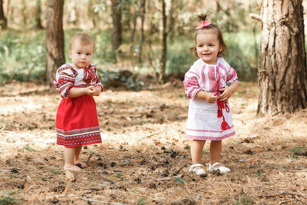 Two baby girls in traditional ukrainian dresses playing in spring forest.