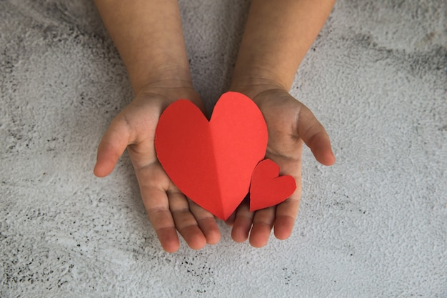 Two baby hands holding red paper hearts.