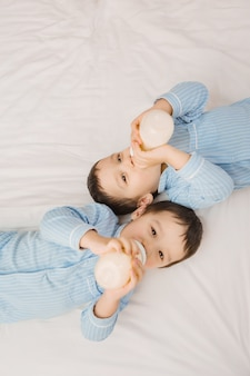 パジャマ姿の双子の男の子2人が、ボトルから牛乳を飲んでベッドに横になります。上からの眺め。結婚と友情の概念。テキストの赤ちゃんfood.spaceの概念