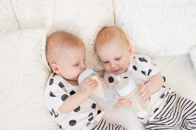 Two baby twins brother and sister 8 months old lie on the bed in their pajamas and drink milk from a bottle, baby food concept, top view, concept of friendship, place for text