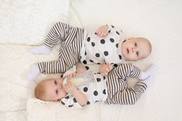 Two baby twins brother and sister 8 months old lie on the bed in their pajamas and drink milk from a bottle, baby food concept, top view, concept of friendship, place for text.