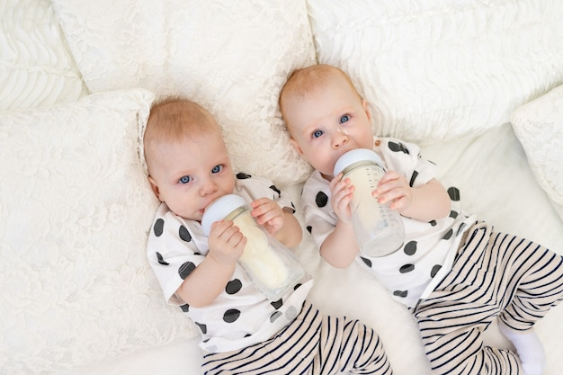 Two baby twins brother and sister lie on the bed in their pajamas and drink milk from a bottle, baby food concept, top view, concept of friendship, place for text