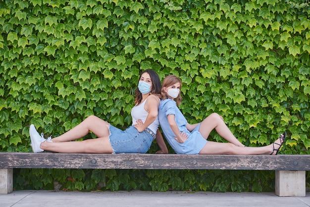 ウイルスマスクを持つ2人の背中合わせの友人