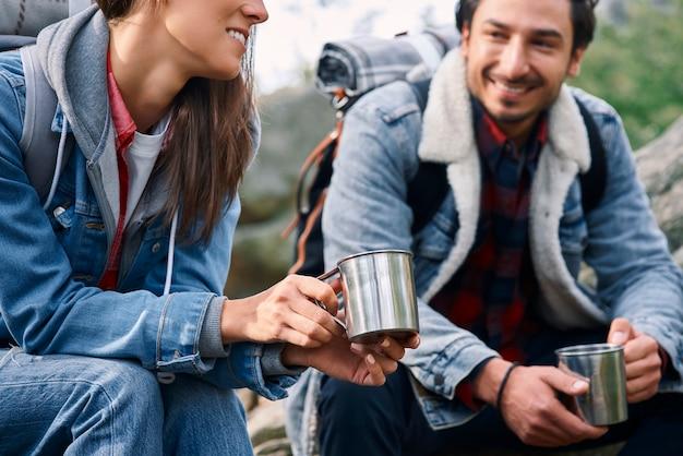 コーヒーを飲みながら話している2人のバックパッカー