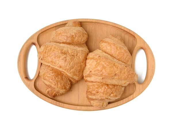 2つの焼きクロワッサンが木製のトレイに横たわって、白い背景で隔離の食品、クローズアップ