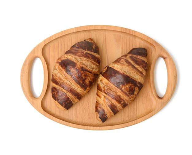 2つの焼きクロワッサンが木製のトレイに横たわっています、白い背景、上面図