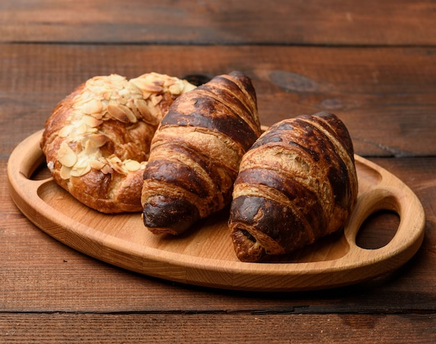 Two baked croissants lie on a wooden tray, food on a brown background