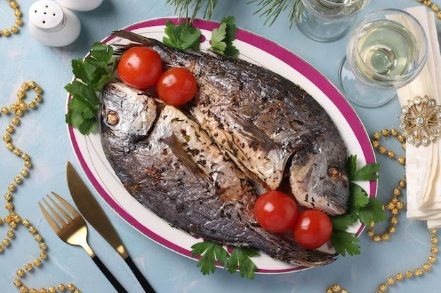 접시에 파슬리와 체리 토마토를 곁들인 향신료를 곁들인 구운 생선 도라도 2개