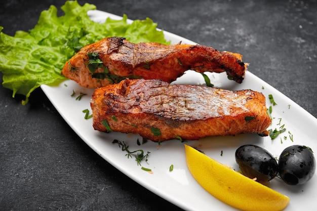 Два запеченных на гриле кусочка лососевой рыбы на белой тарелке с салатом, оливками и лимоном на темном столе