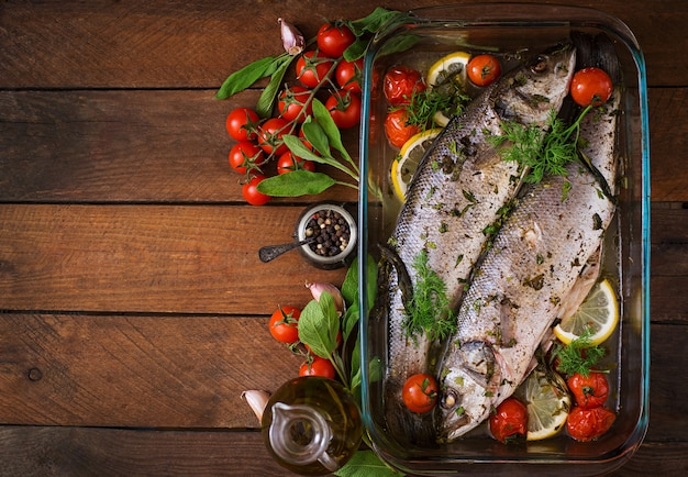 Two baked seabass in a baking dish with spices on an wooden table. top view