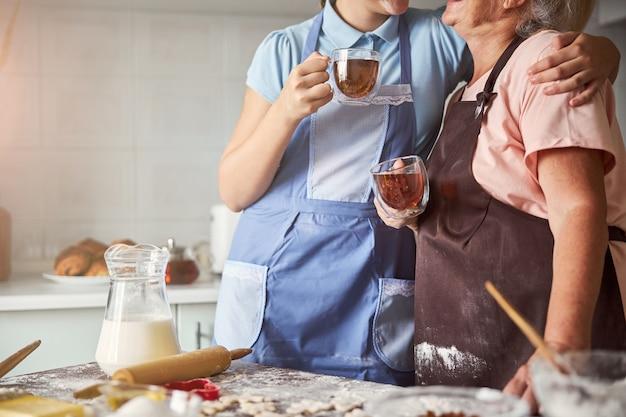 차를 마시고 식탁 근처에서 포옹하는 두 명의 제빵사