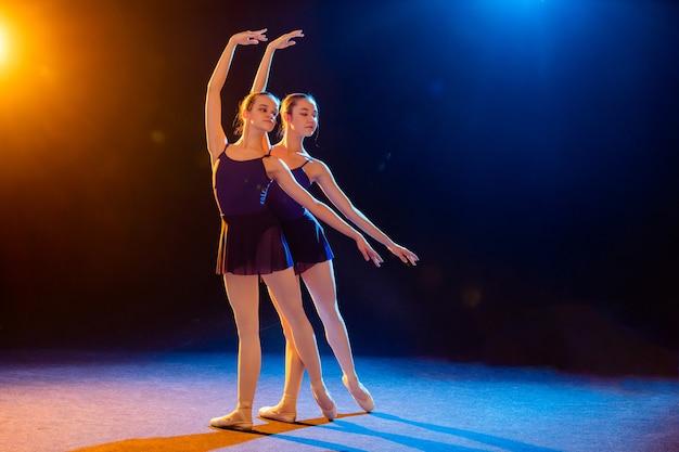 스포트 라이트의 여러 가지 빛깔의 광선으로 조명 된 검은 드레스 포즈의 두 발레리나