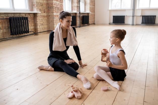 Две балерины сидят на полу после тренировки и вместе обсуждают моменты своего балетного танца