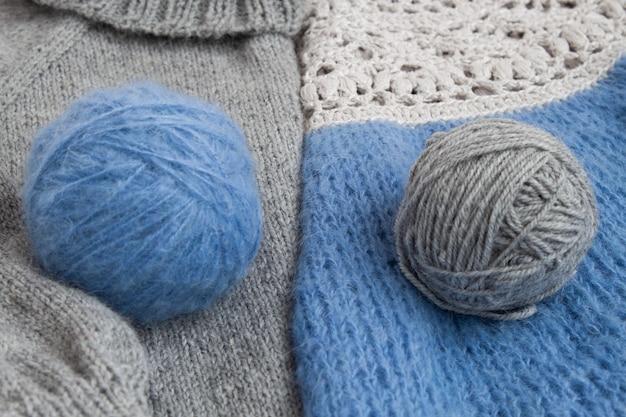 На трикотажном полотне лежат два клубка пряжи для вязания.