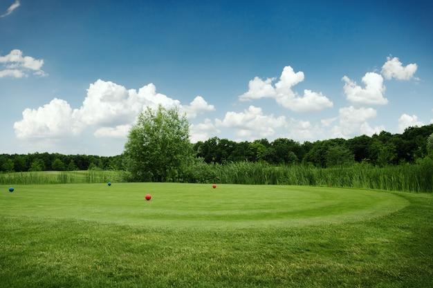 Два мяча на зеленом поле для гольфа, никто