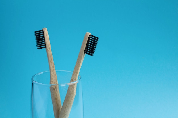 2 бамбуковых зубной щетки в стекле на голубой предпосылке. скопируйте космос. крупный план.
