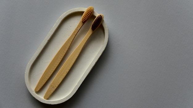 コンクリートトレイに2つの竹の歯ブラシ。灰色の紙の背景。廃棄物ゼロのコンセプト。上面図。コピースペース。