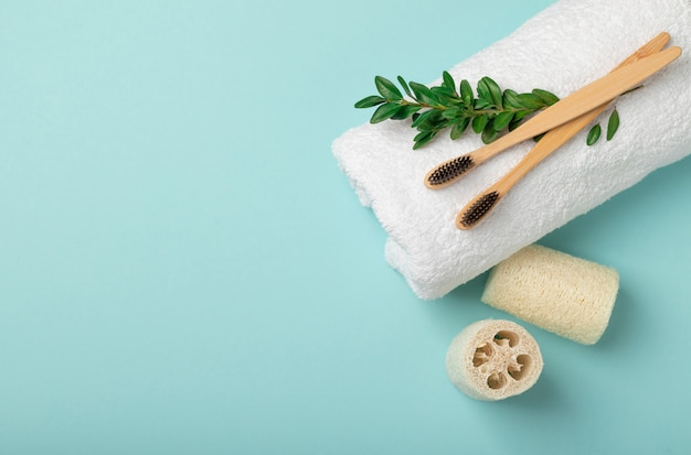 Two bamboo, wooden brushes on a white towel are located on a blue background. loofah washcloths. flat lay with copy space. the concept of medicine, zero waste, recycling, eco friendly.