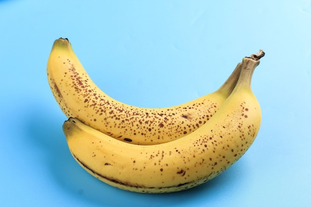 Two banana with freckle on white plate, blue background