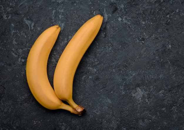 Two bananas on a black concrete table. tropical fruits. trend of minimalism. top view.