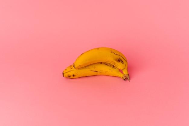 ピンクの背景に分離された2本のバナナ Premium写真