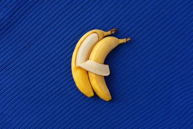 Two bananas lie side by side and hug each other like people.